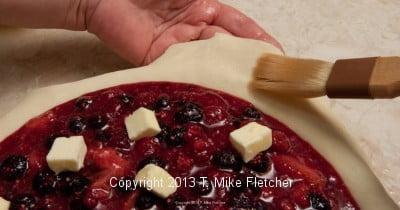 Brushing bottom crust with water