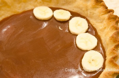 Bananas being placed on caramel for the Double Banana Caramel Cream Pie