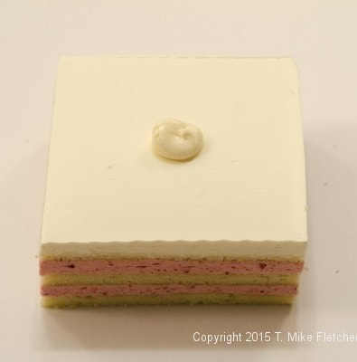 Dot of buttercream on bottom layer