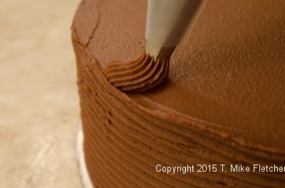 Piping the top of the cake for the Double Chocolate Cake