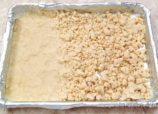 Pressing the crumbs into the pan for the Almond Raspberry Triangles