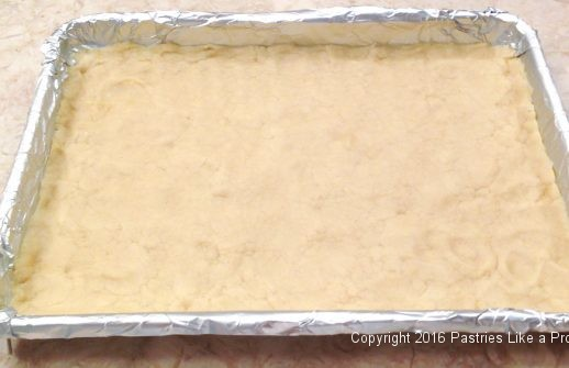 Pressing crust into the pan for the Almond Raspberry Triangles