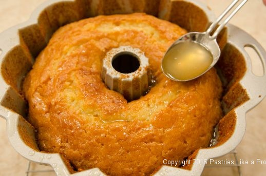 Spooning syrup over cake in the pan for the Lemon Rum Bundt Cake