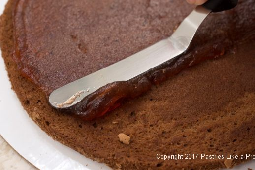 Raspberry jam being spread for the Chocolate Raspberry Marzipan Gateau