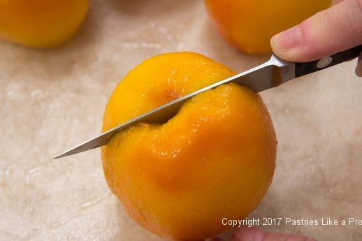 Cutting around the equator of the peach for the White Wine Amaretto Peach Sauce